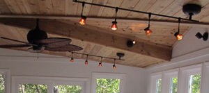 This sunroom has track lighting and ceiling fans for added appeal and convenience