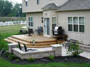 Low to grade deck and patio with built-in bend seating next to grill